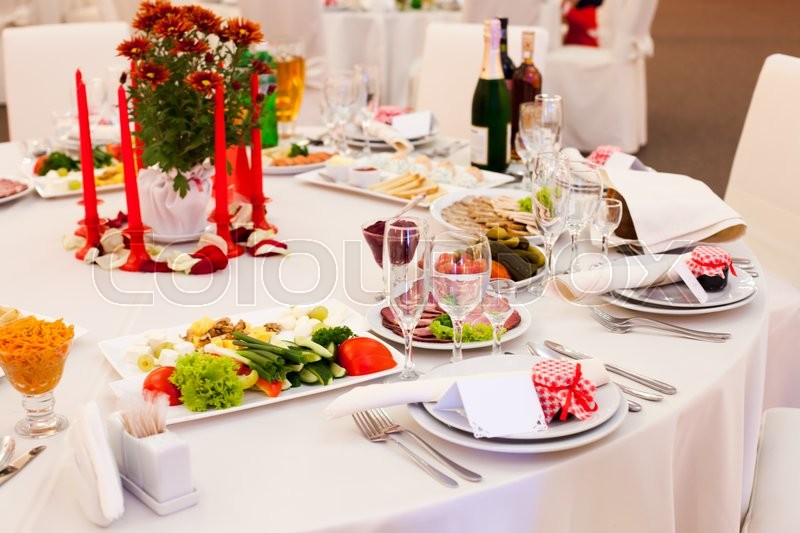 Stock image of 'Table set for a wedding reception in white and red colors with gift on a plate'