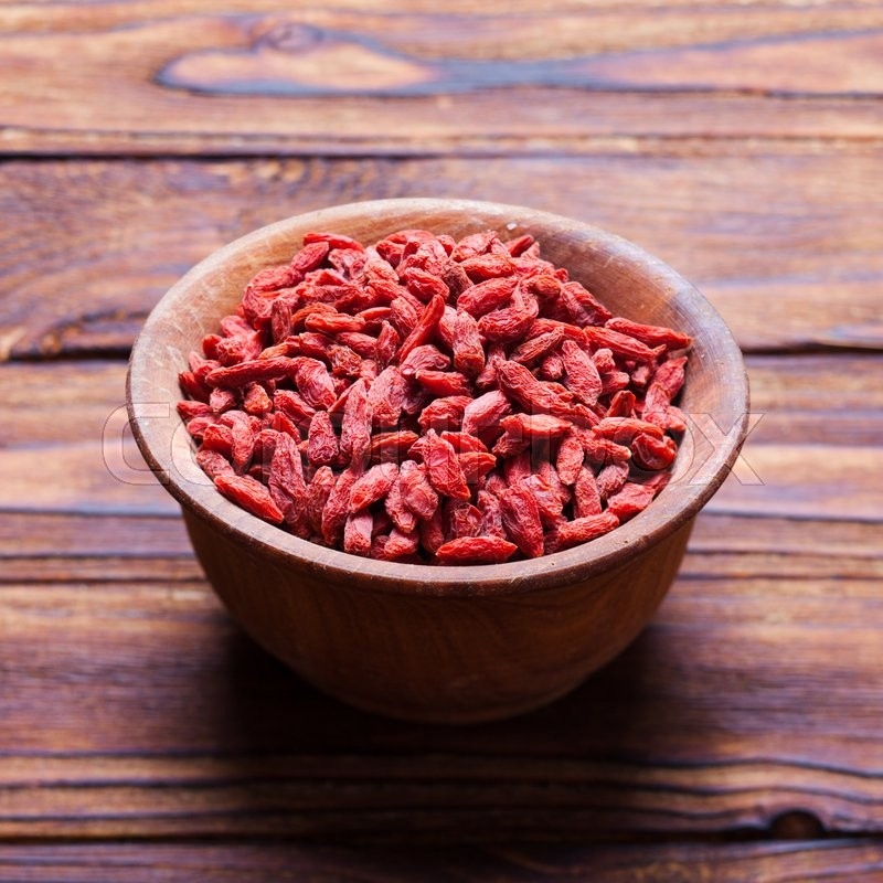 Stock image of 'Red dried goji berries in a wooden bowl'