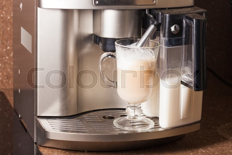 Stock image of 'Coffee machine brewing a cappuccino in glass'