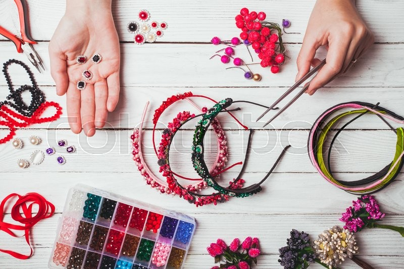 Stock image of 'Plastic berries, flowers, beads and instruments for doing handmade headbands. Top view with hands'