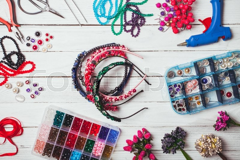 Stock image of 'Plastic berries, flowers, beads and instruments for doing handmade headbands. Top view'