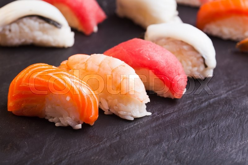 Stock image of 'Close-up of set of four sushi with salmon, tuna, scallop and shrimp on a black background'