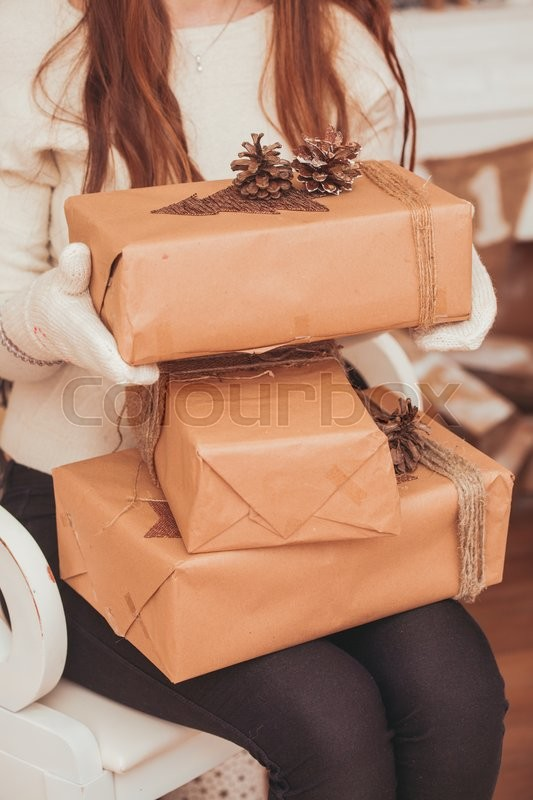 Stock image of 'Girl in gloves holding  gift boxes on her knees near Christmas tree'