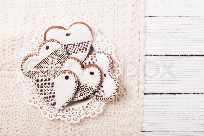 Stock image of 'Gingerbread cookies in shape of heart with icing on a crochet doily'