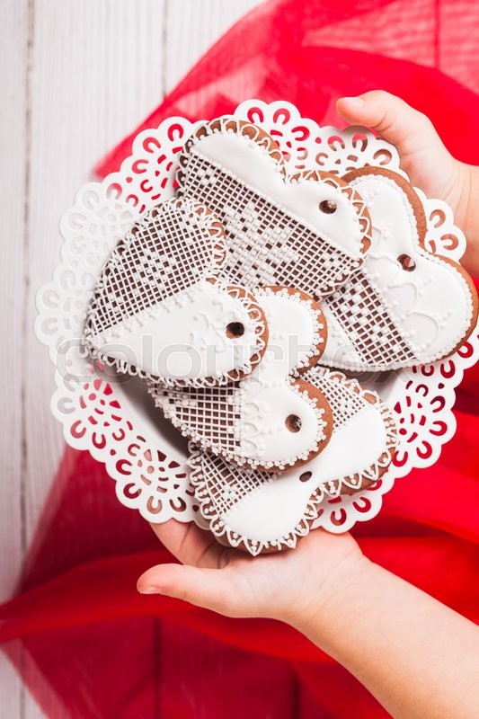 Stock image of 'Gingerbread cookies in shape of heart in girl's hands'