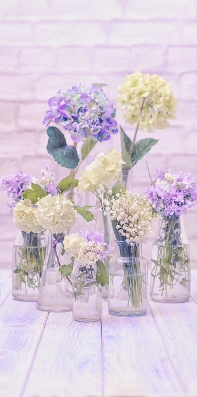 Stock image of 'Flowers in bottles over white wall, vintage styled wallpaper'