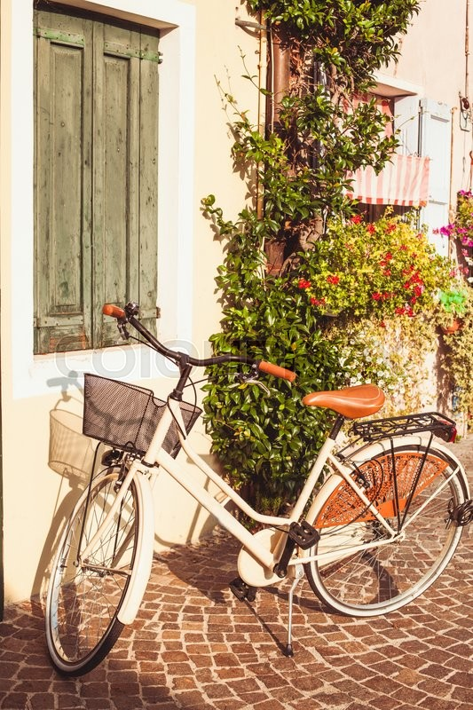 Stock image of 'White vintage bicycle with basket on vintage house wall in Italy'