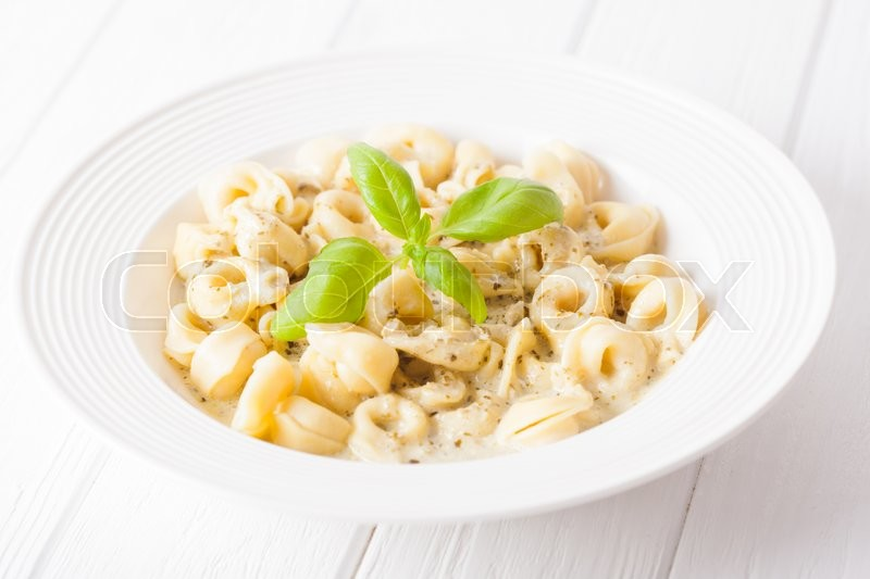 Stock image of 'Delicious dish of tortellini with pesto in white plate'