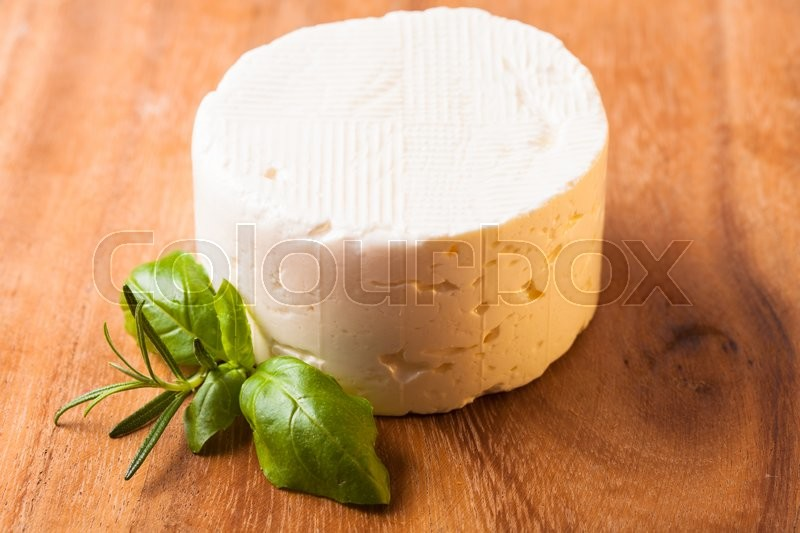 Stock image of 'Salted soft cheese with basil leaf on the board'