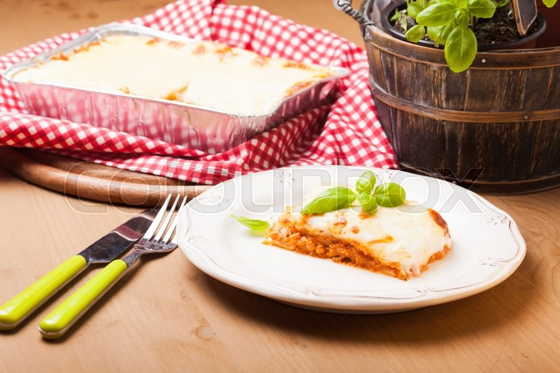 Stock image of 'Piece of lasagna bolognese with basil leaves in a white plate'