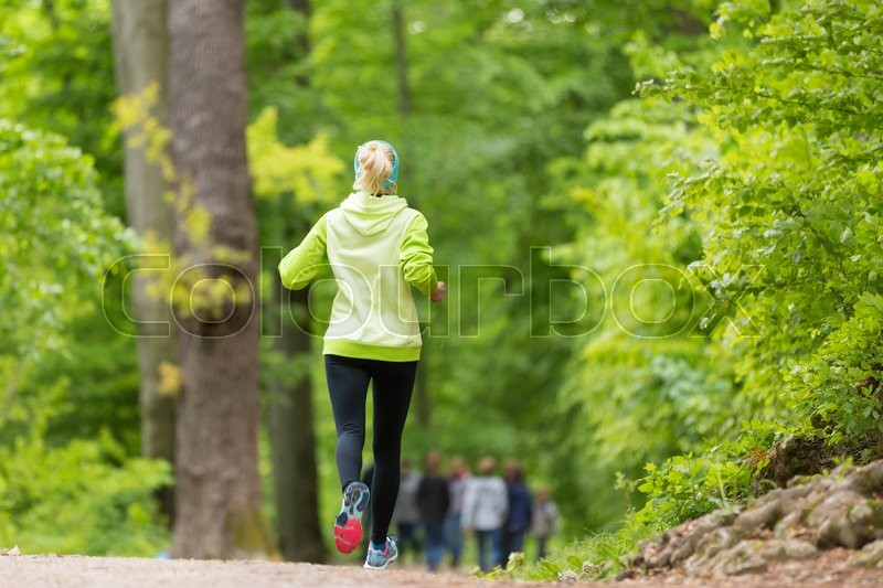 Stock image of 'Sporty young female runner in forest.  Running woman. Female runner during outdoor workout in nature. Fitness model outdoors. Weight Loss. Healthy lifestyle. '