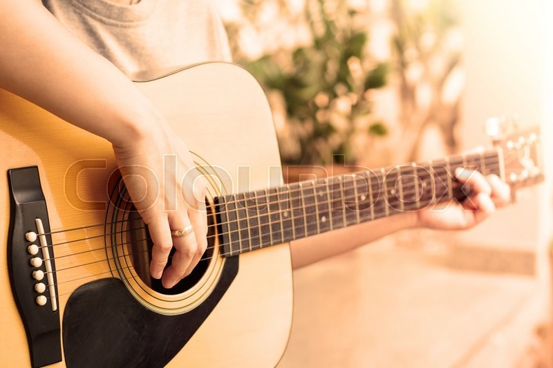 Stock image of 'Woman's hands playing acoustic guitar with vintage style, stock photo'