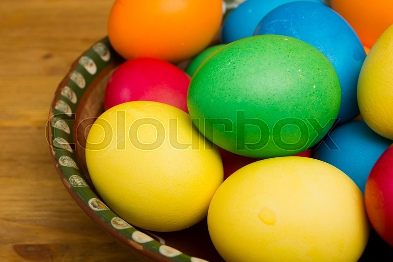 Stock image of 'Easter eggs of different colors on a wooden background'