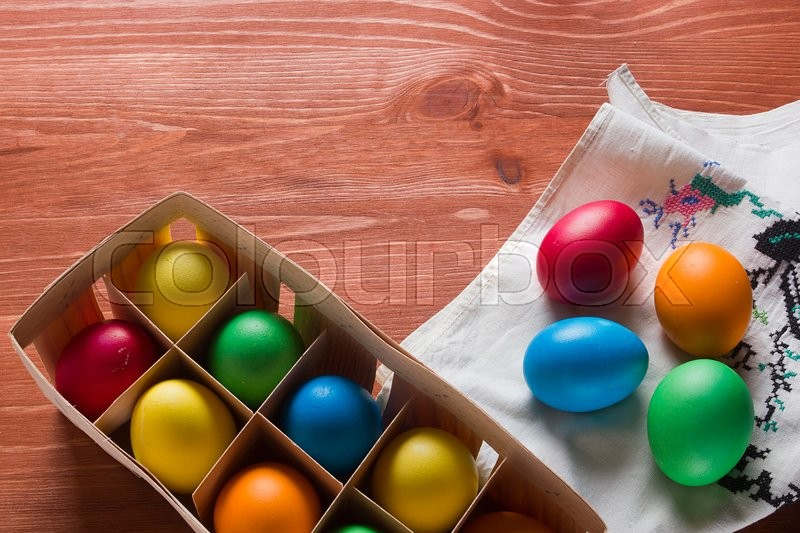 Stock image of 'Easter colored eggs and a napkin with embroidery on the wooden table'