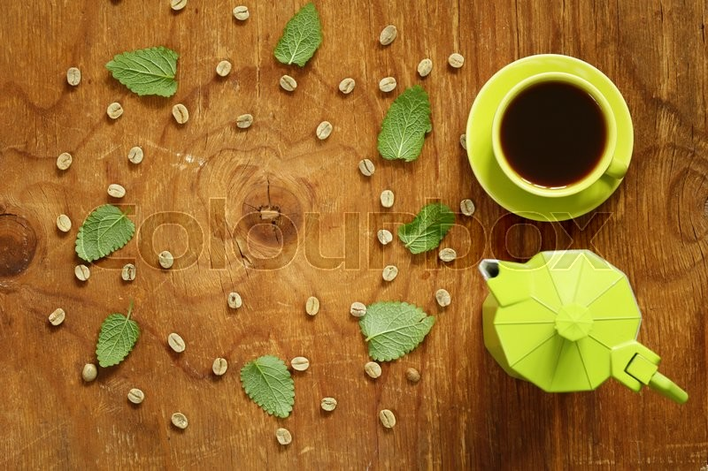 Stock image of 'Coffee pattern green coffee beans and mint leaves on a wooden background'