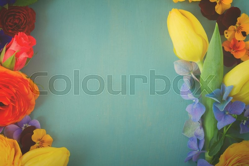 Stock image of 'Flowers  frame with copy space on blue wooden table, retro toned'