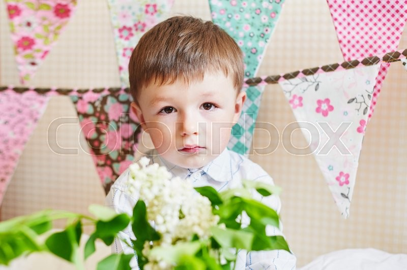 Stock image of 'little boy with colorful flags on the background.'