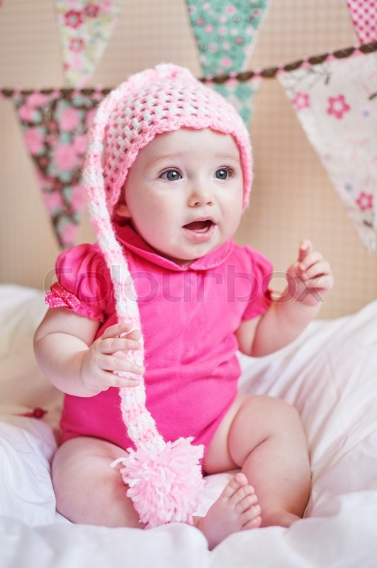 Stock image of 'newborn baby girl in pink knitted hat on the bed.'