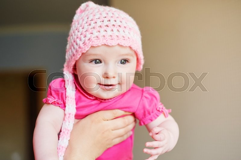 Stock image of 'little baby girl in a knitted hat on hands at mum.'