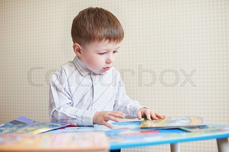Stock image of 'Little boy is sitting at the desk and read book.'