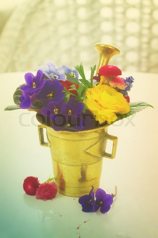 Stock image of 'Fresh flowers in vintage mortar, herbal medicine, retro toned'