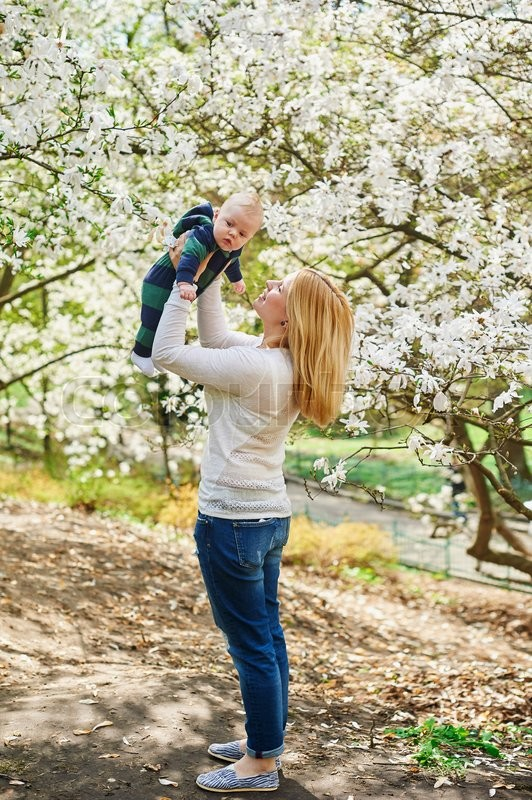 Stock image of 'Little baby boy with young mother in the spring blossom garden.'