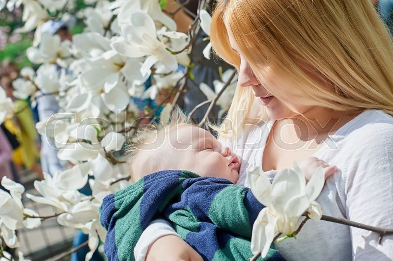Stock image of 'mother with her baby son in her arms sitting on a tree branch in a spring garden.'