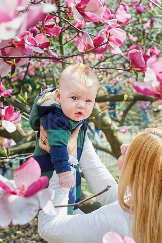 Stock image of 'mother walking with her baby son in garden of blooming magnolias.'