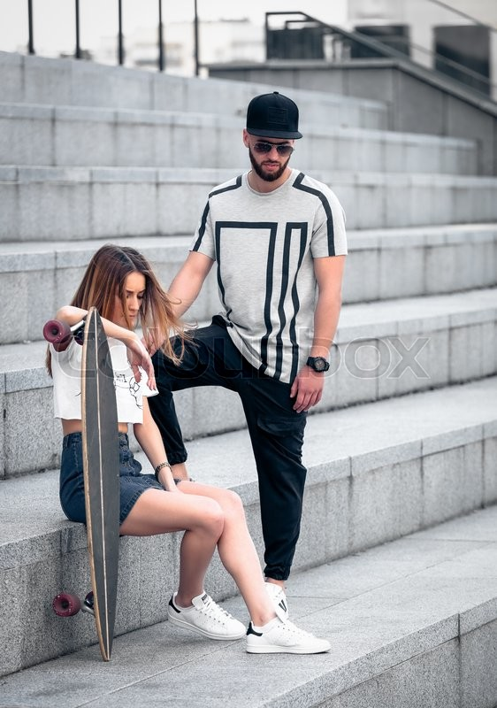 Stock image of 'Young modern stylish hipsters couple on the concrete levels. Fashion couple looking down. Stylish hipster girl hold a longboard. Fashion young man in sunglasses.'