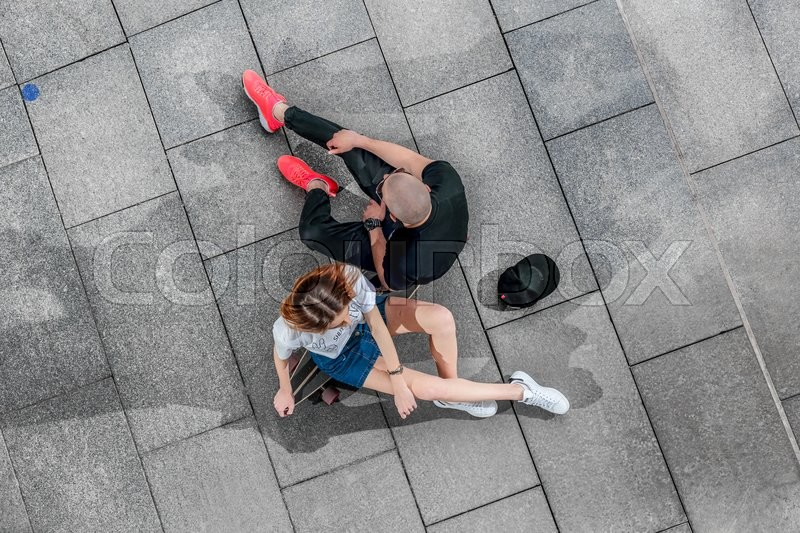 Stock image of 'Top view of a man and woman sitting on a longboard on a concrete surface. Stylish and fashionable couple, shoot in a urban location.'
