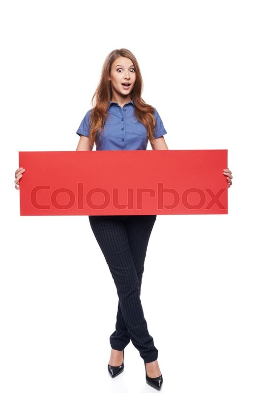 Stock image of 'Full length surprised young woman holding red blank cardboard, over white background'