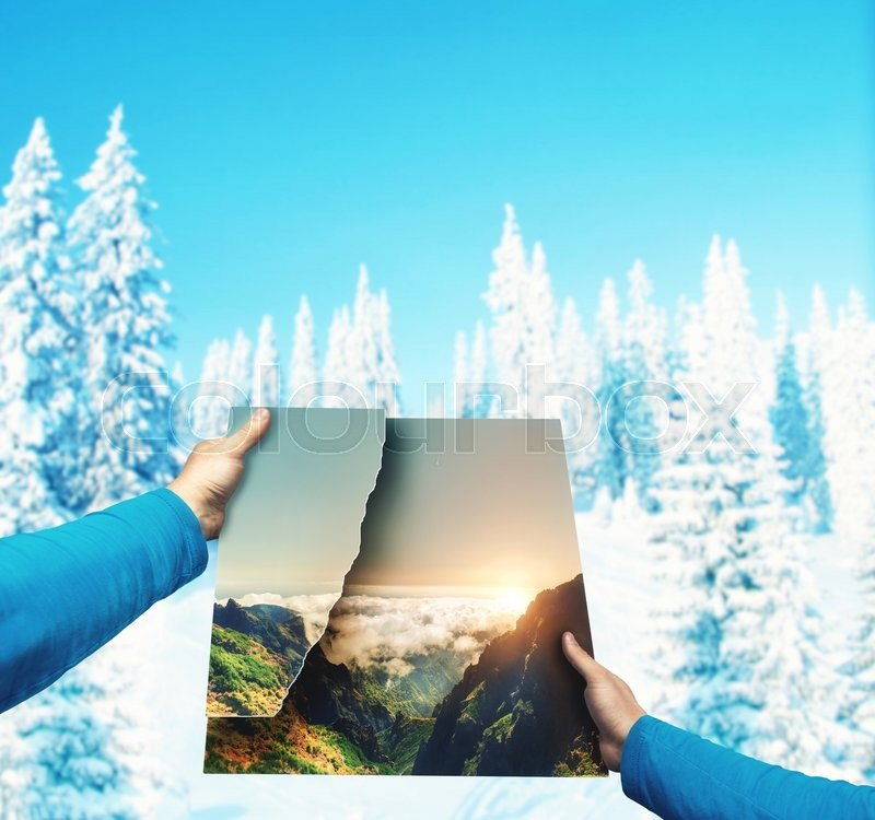 Stock image of 'Male hands holding picture of summer landscape against winter mountains'