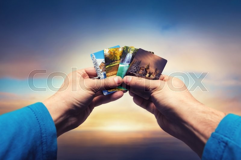 Stock image of 'Male hands holding cards with four seasons landscapes over the sky'