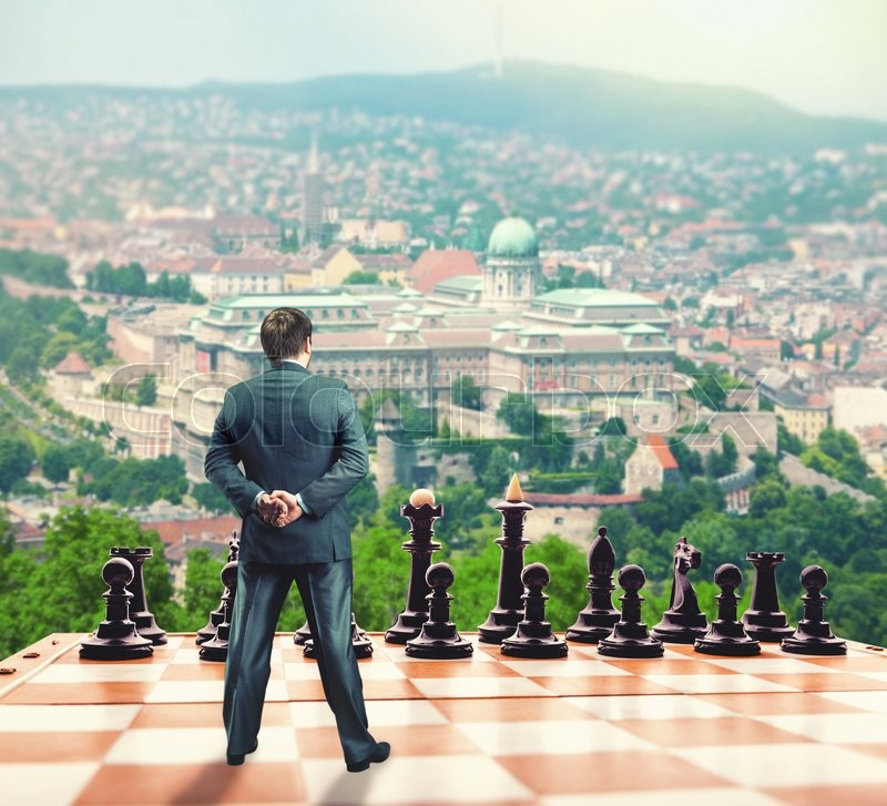 Stock image of 'Businessman standing in front of the black team on the chess board '
