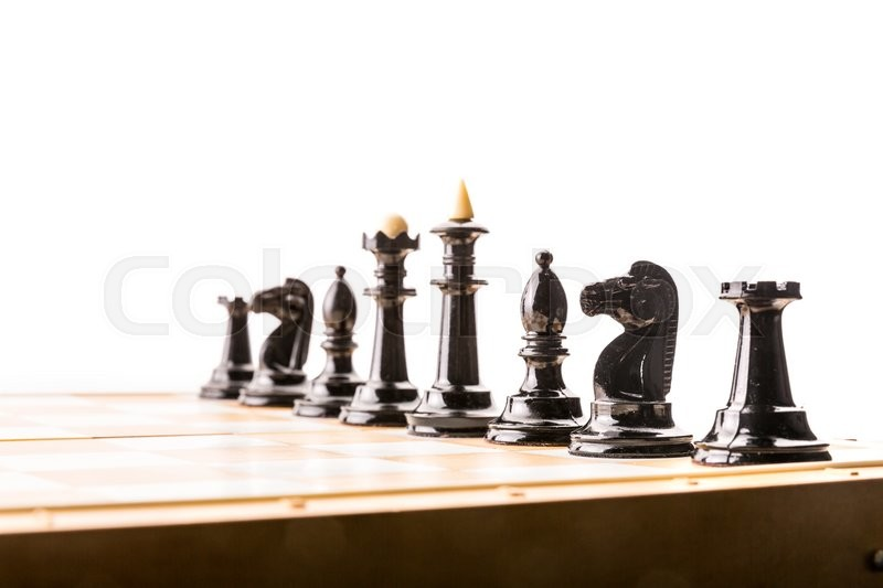 Stock image of 'Black chess figures on the board ready to fight. Isolated'