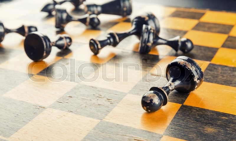 Stock image of 'Old wood chess figures lying on the board defeated'