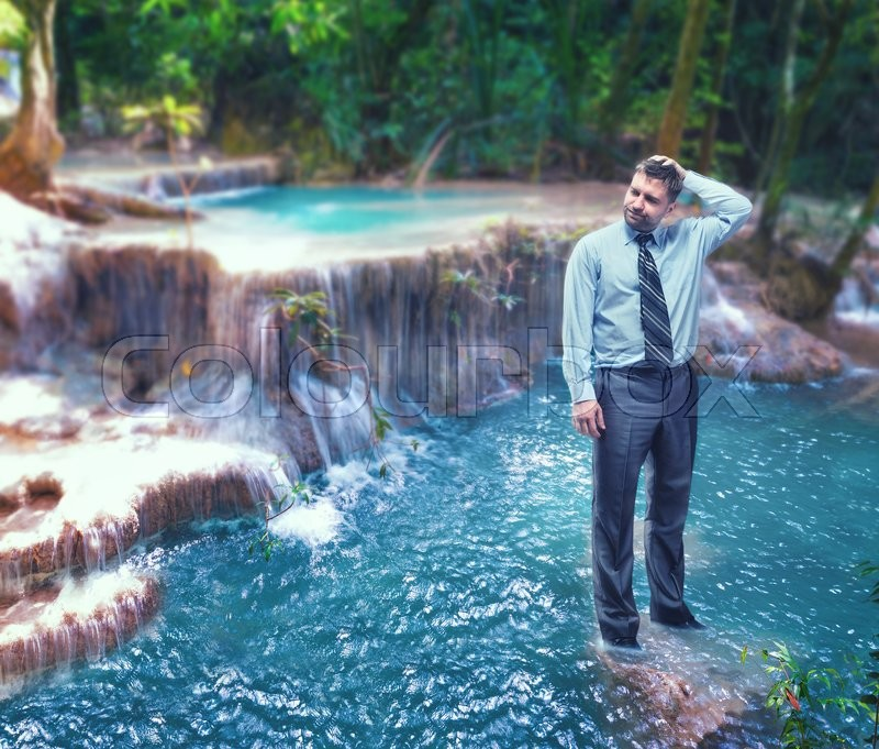 Stock image of 'Troubled businessman standing in the waterfall'
