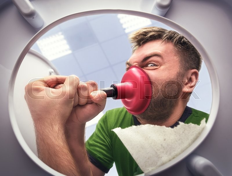Stock image of 'Man cleaning the toilet with cup plunger'