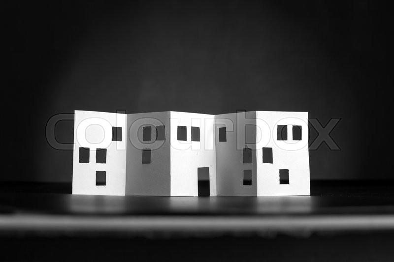 Stock image of 'White paper building with cut windows and doors over black'