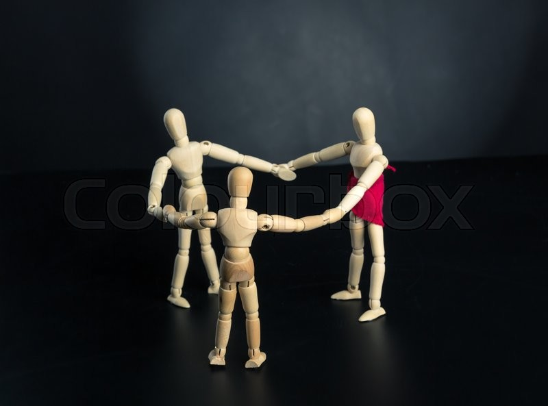 Stock image of 'Family of wooden figures standing in circle over black background'