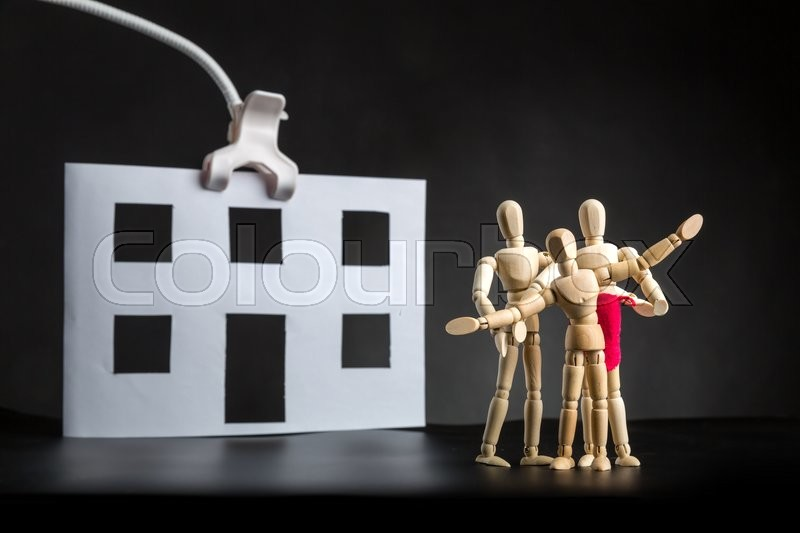 Stock image of 'Family of wooden figures near paper house'