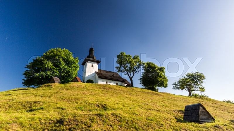 Stock image of 'View of a typical old slovak church in the village Martincek near Ruzomberok, Slovakia in summer 2015'