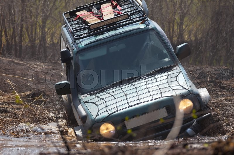 Stock image of 'Suzuki Jimny crossing water obstacle or a swamp'