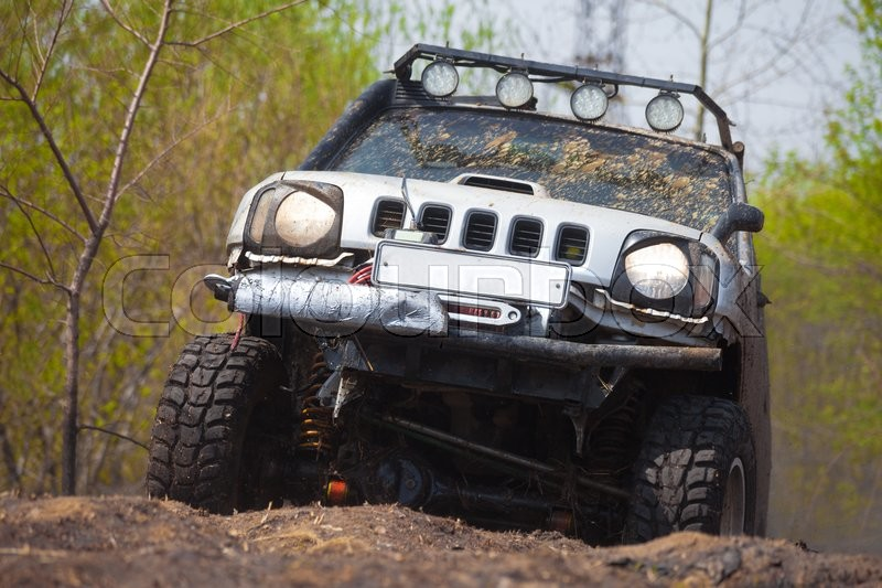 Stock image of 'Suzuki Jimny cross country moving in spring forest'
