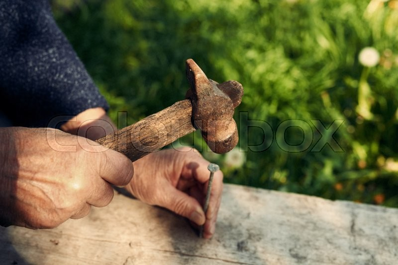 Stock image of 'Closeup of mature man hands nails with old hammer an old weathered wooden plank outdoors against green grass background, cropped image'