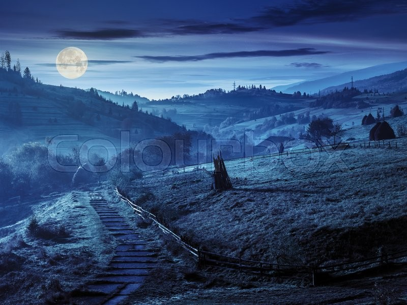 Stone steps down the hill in to village in foggy mountains at night in full moon light, stock photo