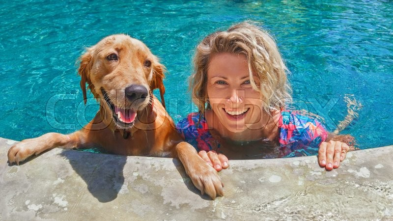 Funny portrait of smiling woman playing with dog and training golden retriever puppy in blue swimming pool. Popular dog breeds, outdoor activity and fun games with family pet on summer beach holiday, stock photo