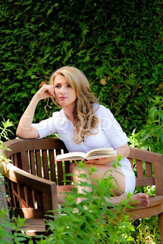 Woman Reading A Book In The Garden Stock Photo Colourbox