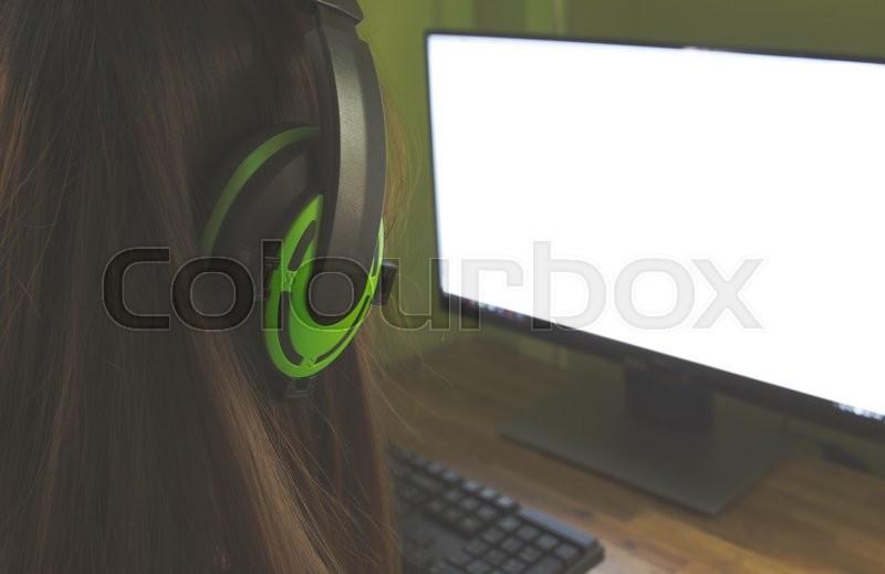 Students working in computer class wearing headphones in college, stock photo