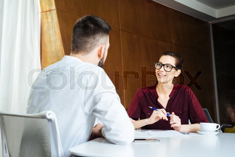Stock image of 'Smiling beautiful businesswoman in glasses talking to young businessman in meeting room'